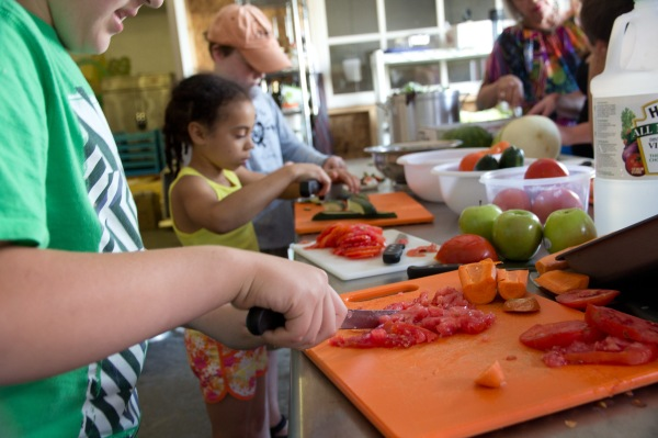 Kids at the Carrot Academy chop up tomatoes for lunch.